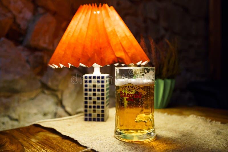 萨比莱,拉脱维亚- 2019年4月21日:杯在Krogs餐馆的Uzavas低度黄啤酒 免版税图库摄影