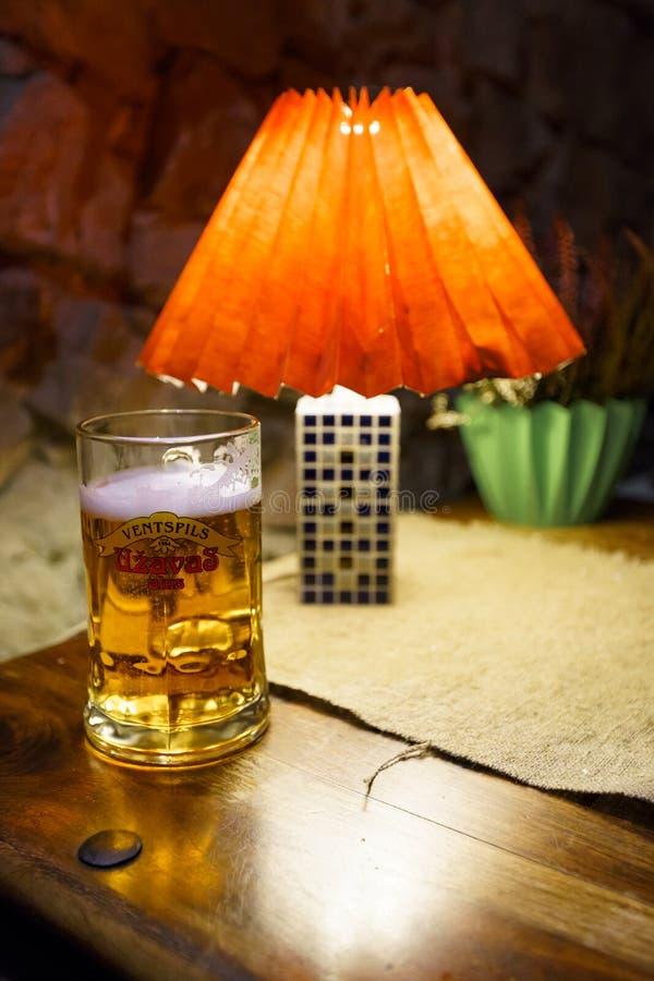 萨比莱,拉脱维亚- 2019年4月21日:杯在Krogs餐馆的Uzavas低度黄啤酒 库存照片