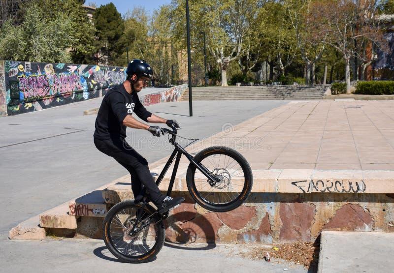 萨瓦格萨,西班牙;03 23 2019年:体育人佩带的盔甲、T恤杉、手套和长裤在黑骑马bmx自行车起来 库存照片
