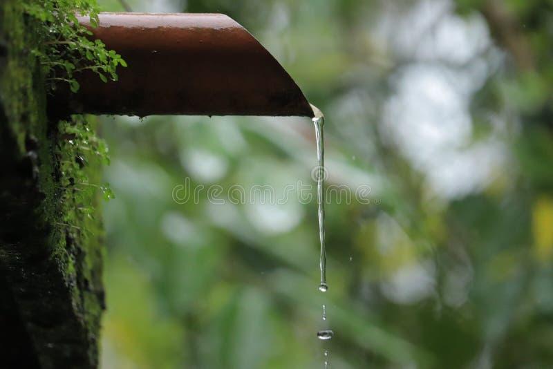 落下从橙色管子的水 免版税库存图片