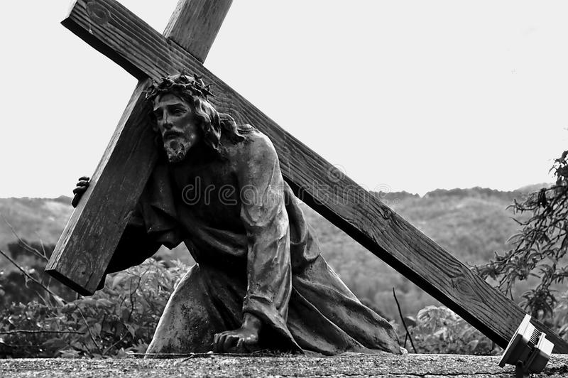 落与十字架的耶稣基督雕象 图库摄影