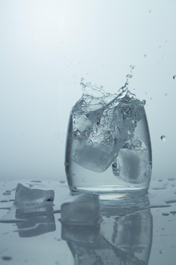 落与在一块透明玻璃的飞溅的冰用水 冰水纯净的飞溅  特写镜头,轻的背景 免版税库存图片