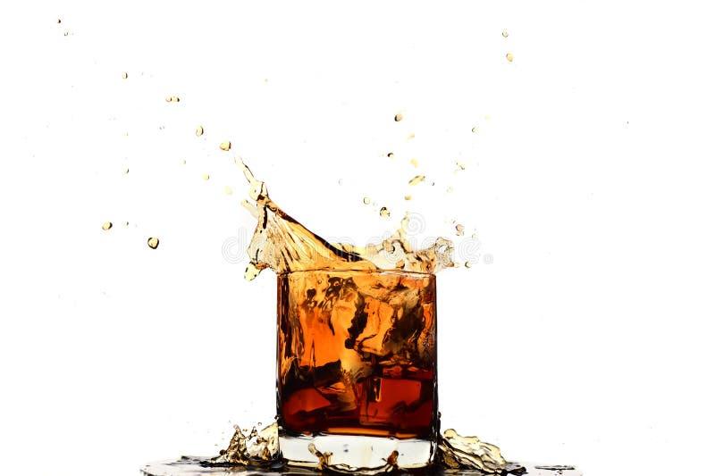 落入在玻璃的威士忌酒的冰块 免版税库存照片