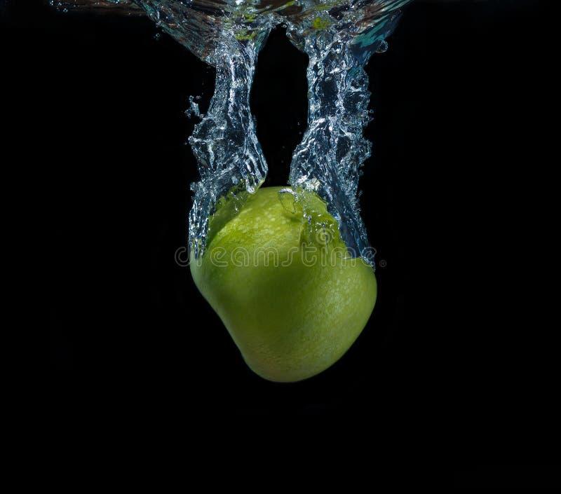 落入在黑背景的水的绿色苹果 免版税库存照片