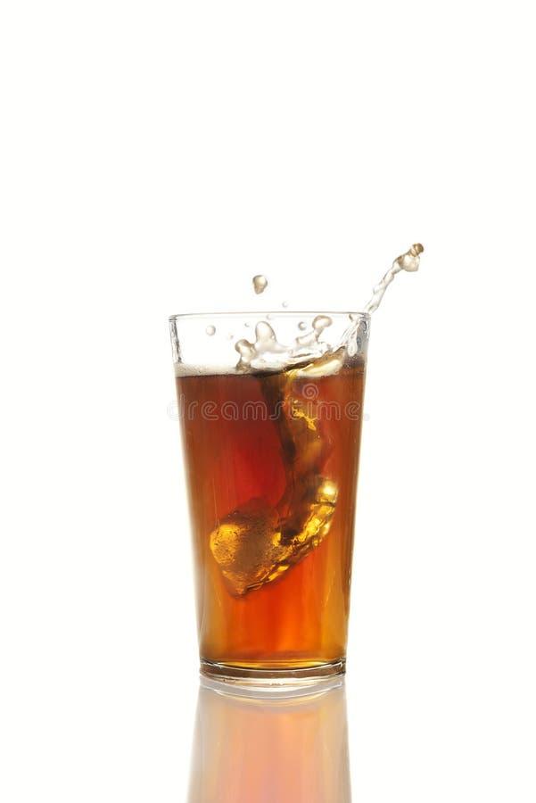 落入杯的冰块可乐 免版税库存图片