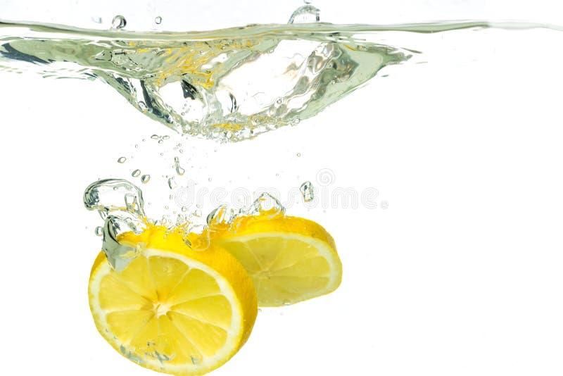 落入水和飞溅的柠檬切片和石灰在白色背景 免版税库存图片