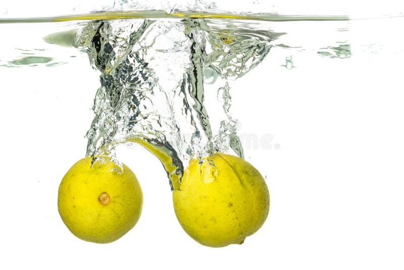 落入水和飞溅的柠檬切片和石灰在白色背景 库存照片