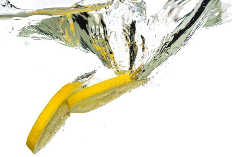 落入水和飞溅的柠檬切片和石灰在白色背景 库存图片