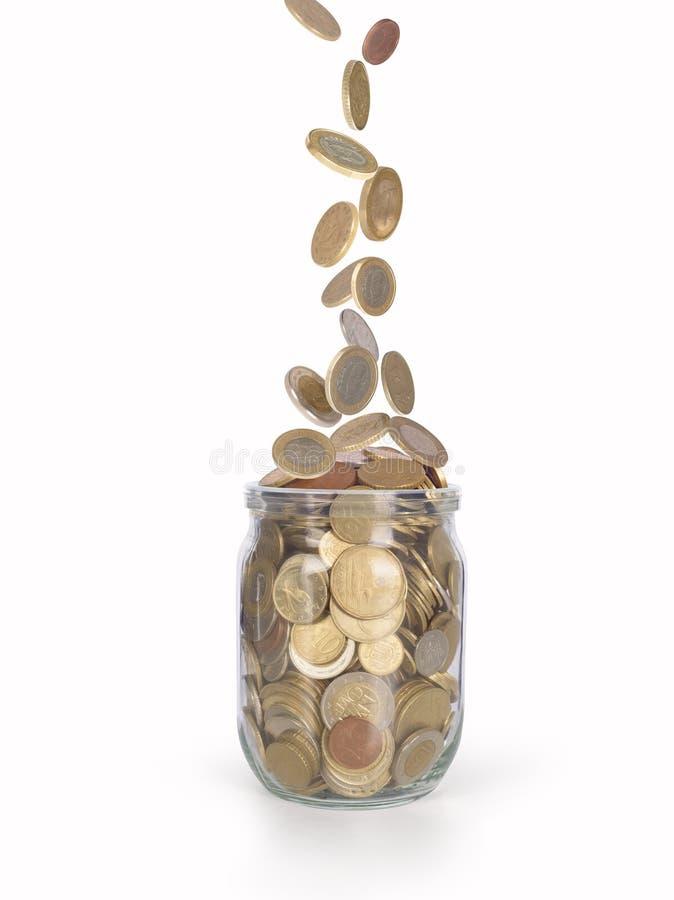 落入玻璃瓶子的硬币 免版税库存图片