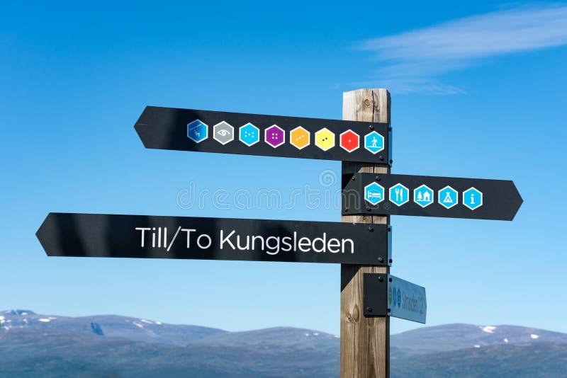 落后显示Kungsleden供徒步旅行的小道的方向的标志标志 库存照片