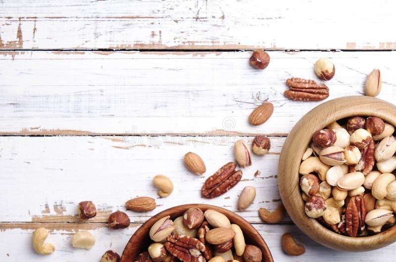 落后用不同的种类的混合在棕色木碗的坚果在被抓的白色木桌背景,软的白天 复制空间 库存图片