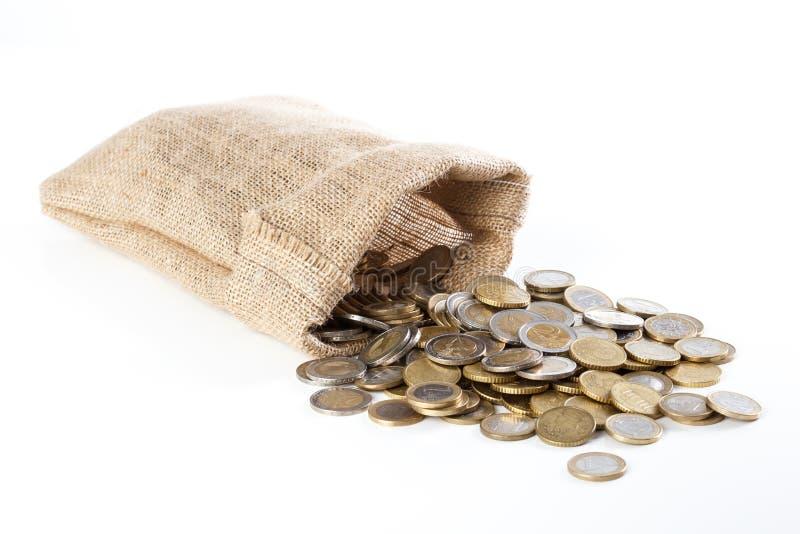 落在一个小粗麻布大袋外面的硬币,在白色  库存照片