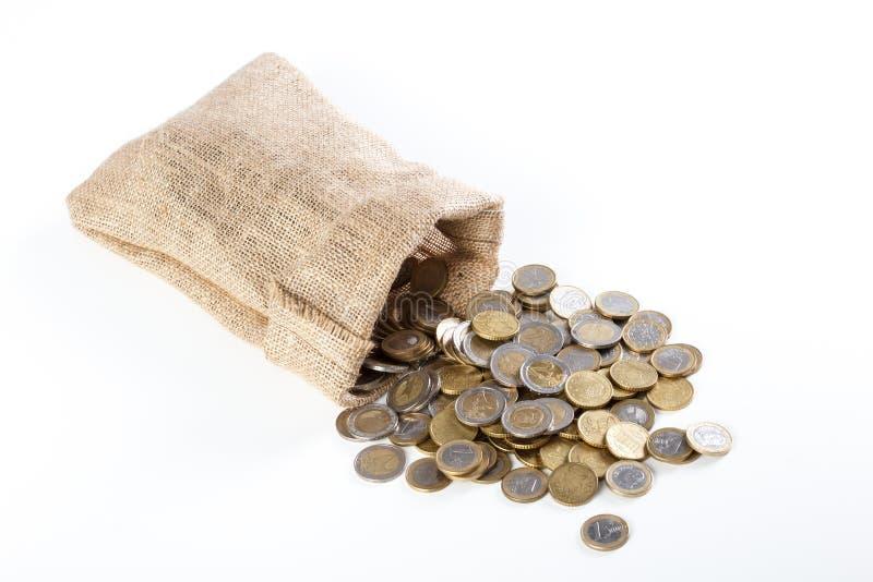 落在一个小粗麻布大袋外面的硬币,在白色  免版税库存照片