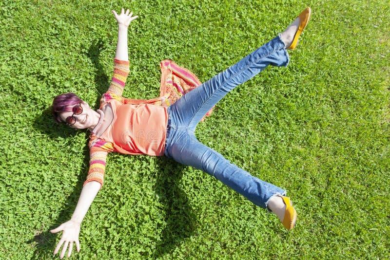 落在与她的被伸出的胳膊的草的快乐的女孩 库存图片