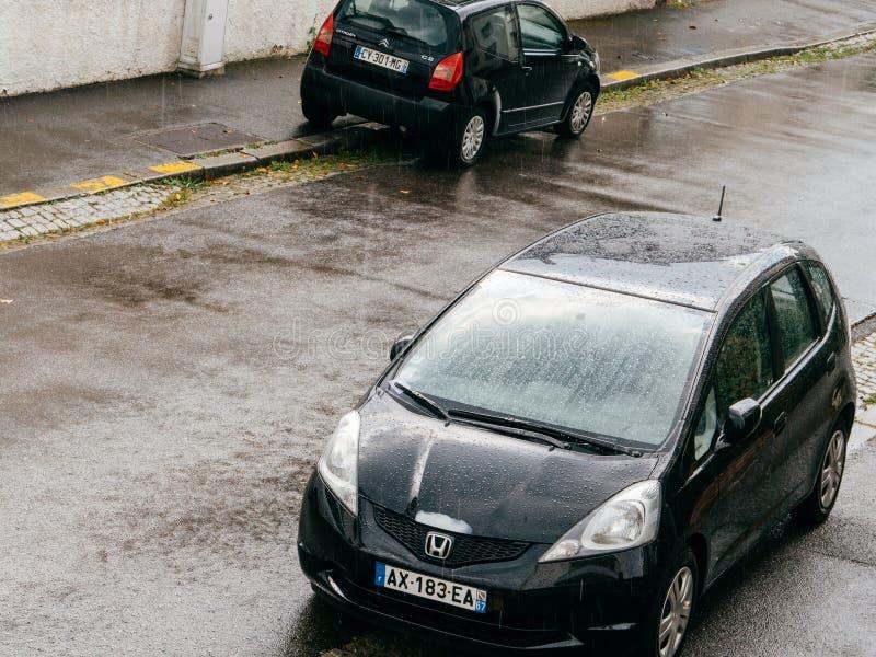 落在本田飞度汽车和雪铁龙C2的大雨 库存图片