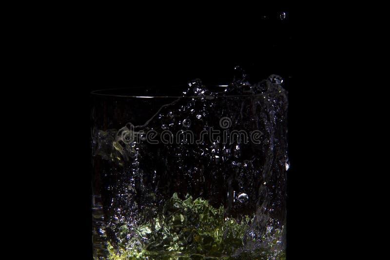 落在白色的水中的绿色硬花甘蓝用气泡硬花甘蓝在水,冻结时间中,飞溅水 免版税库存照片