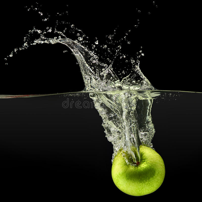 落在黑背景的水中的绿色苹果 库存图片
