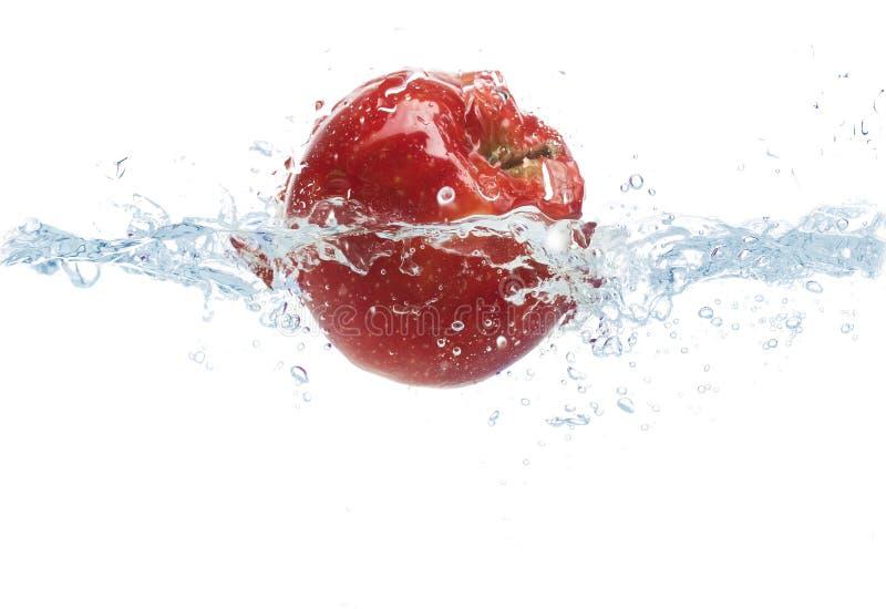 落或浸洗在与飞溅的水中的苹果计算机 免版税库存图片