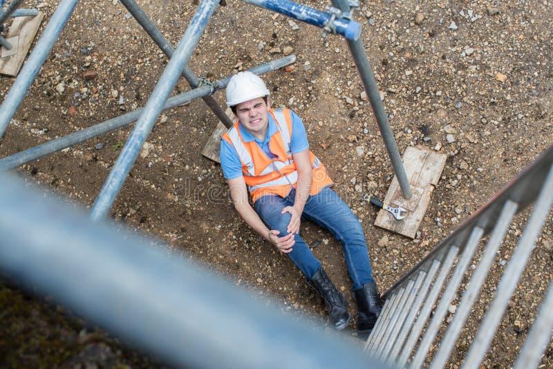 落梯子和腿受伤的建筑工人 免版税库存照片