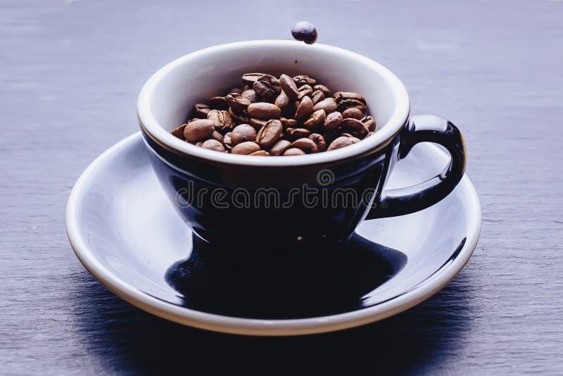 落的咖啡豆托起 免版税库存照片