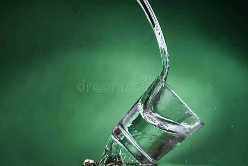 落的小玻璃和溢出在绿色背景的水 库存照片