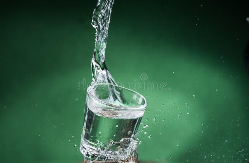 落的小玻璃和溢出在绿色背景的水 免版税库存照片