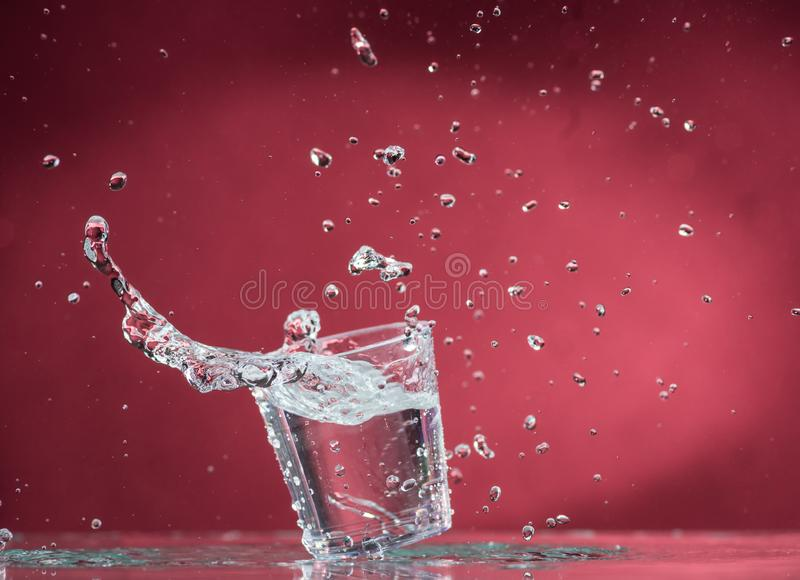 落的小玻璃和溢出在蓝色背景的水 免版税图库摄影