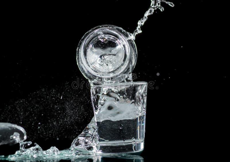 落的小玻璃和溢出在黑背景的水 免版税图库摄影