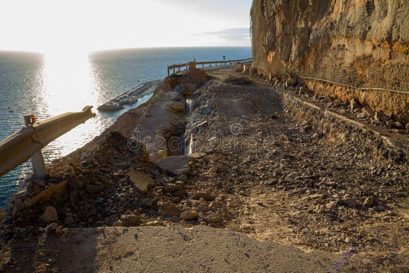 落的岩石和大崩溃孔在闭合的山路在海下 库存照片
