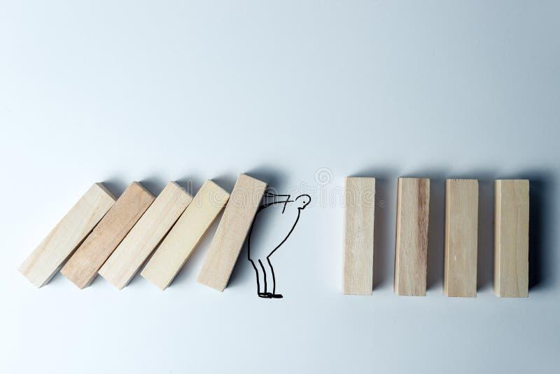 落的木立方体和拿着他们绘了人,作为支持、正确的决定和领导的标志,在参差不齐的白色 免版税库存图片