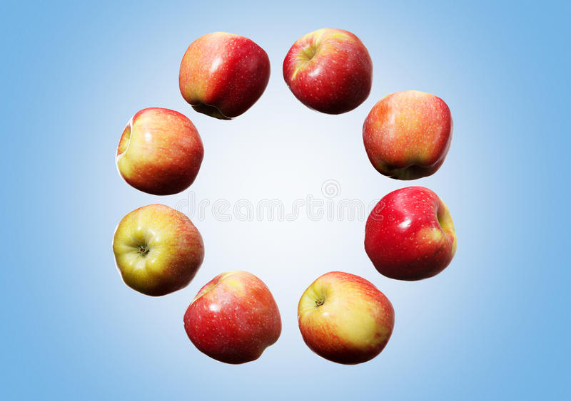 落的红色和黄色苹果圈子在天空中在蓝色背景 库存照片