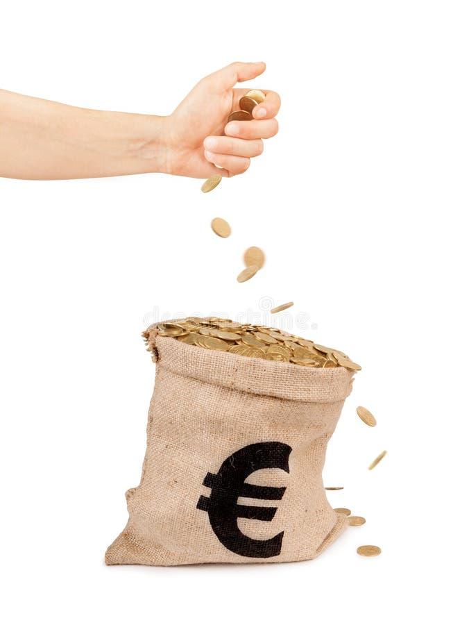 落从手的硬币入与硬币的袋子 免版税图库摄影
