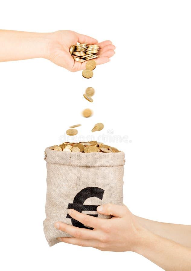 落从手的硬币入与硬币的袋子 库存照片