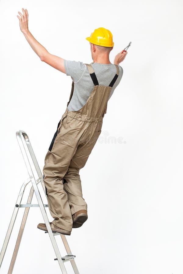 落从梯子的工作者 库存照片