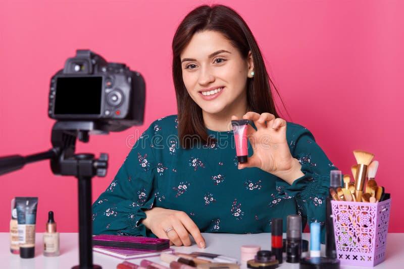 著名博客作者 快乐的女性显示的化妆用品产品,当记录录影和给她的秀丽博克的忠告,看时 免版税图库摄影