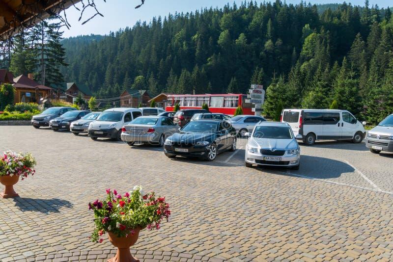 著名品牌汽车在停车场的在旅馆附近和在他们后一辆游览车 一切位于a 库存照片