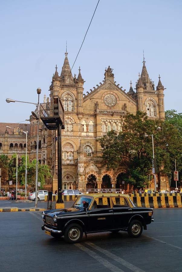 著名孟买黄色黑出租汽车汽车和在背景Chhatrapat 免版税库存照片