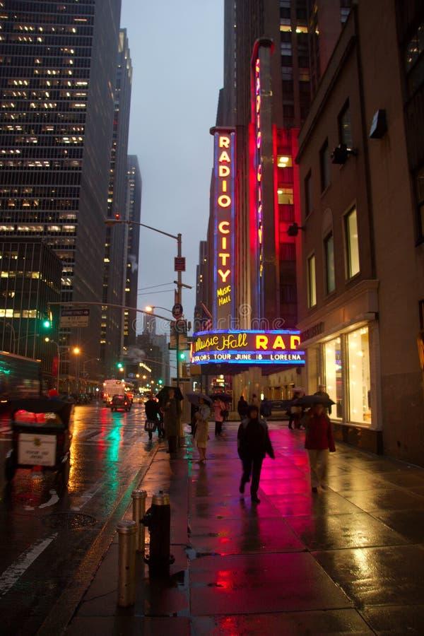 著名无线电城音乐厅的霓虹灯广告在一条湿边路反射了 库存照片