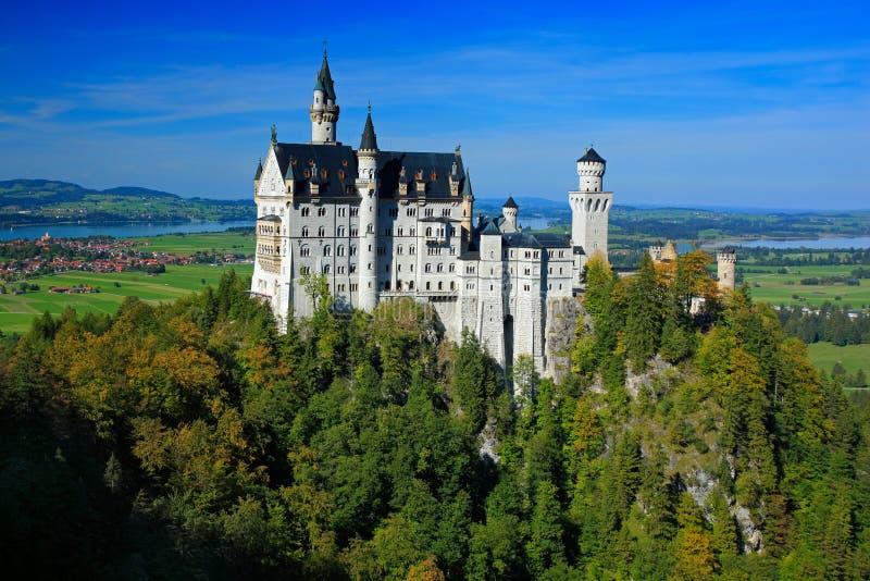 著名童话新天鹅堡城堡在巴伐利亚,德国,与蓝天的下午 免版税库存图片