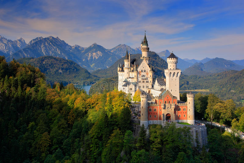 著名童话新天鹅堡城堡在巴伐利亚,德国,与蓝天的黄昏与白色云彩 库存图片