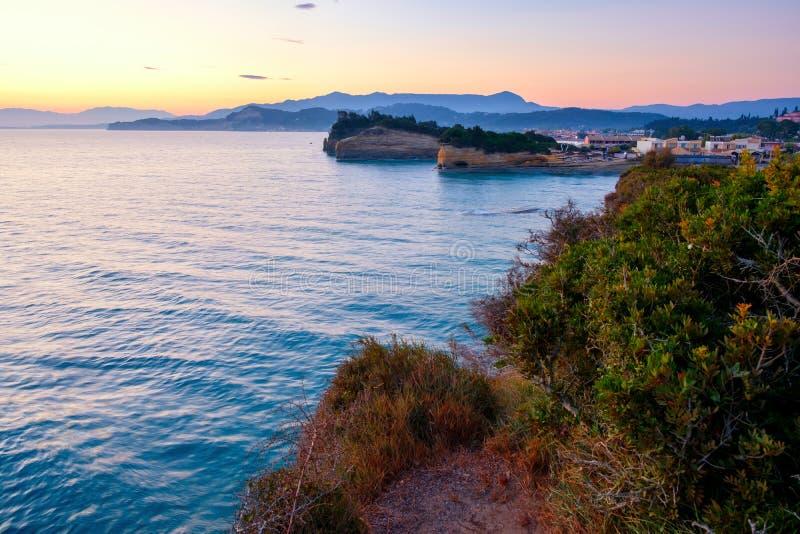著名运河d'与美好的岩石海岸线的私通海滩在使日出的蓝色爱奥尼亚海惊奇在希达利Corf的假日村庄 图库摄影