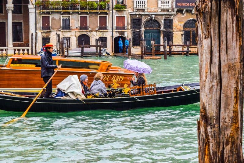 著名长平底船小船乘驾的女性游人在雨期间在有平底船的船夫佩带的草帽的城市,站立与荡桨桨 免版税库存照片