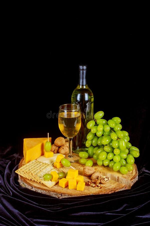 葡萄、乳酪、无花果和蜂蜜与一杯白葡萄酒在木背景 库存图片