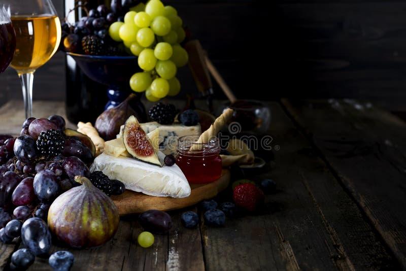 葡萄、乳酪、无花果和蜂蜜与一杯白葡萄酒 免版税图库摄影