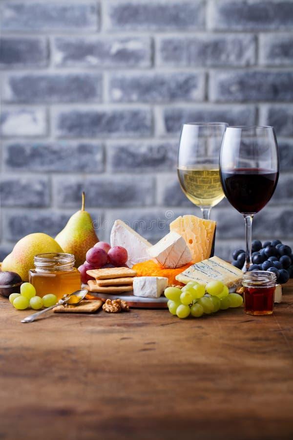葡萄、乳酪、无花果和蜂蜜与一杯红色和白酒 r 免版税库存图片