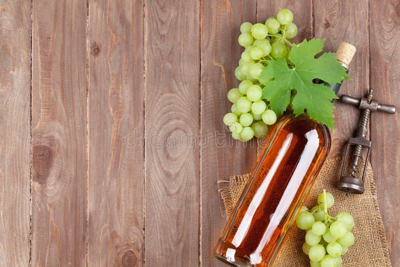 葡萄、白葡萄酒瓶和拔塞螺旋 免版税库存图片