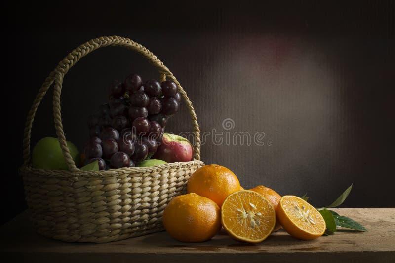 葡萄、苹果和桔子在a在柳条筐在木ta 免版税库存照片