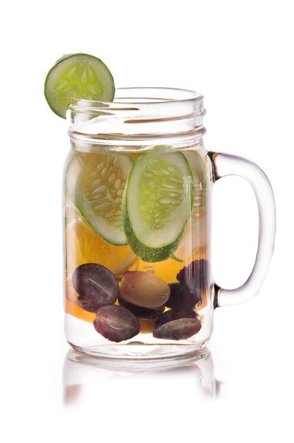 葡萄、黄瓜和桔子被灌输的新鲜水果水  孤立 免版税库存图片