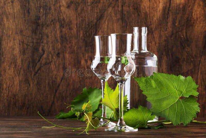 葡萄伏特加酒,pisco -在典雅的玻璃的传统秘鲁强的酒精饮料在葡萄酒木桌,拷贝空间上 库存照片