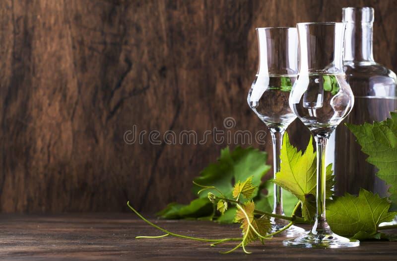 葡萄伏特加酒,pisco -在典雅的玻璃的传统秘鲁强的酒精饮料在葡萄酒木桌,拷贝空间上 免版税库存图片